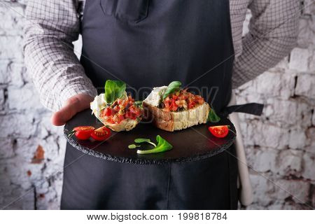 Chef suggesting exquisite restaurant appetizer. Crusty bruschetta with concasse tomatoes, stracciatella cheese decorated with spinach in unrecognizable male hands. Copy space on apron or brick wall