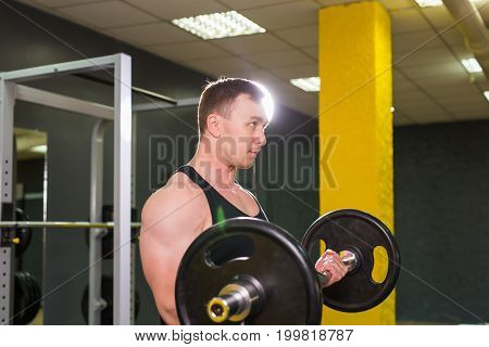 Strong and handsome man lifting weights a barbell in a gym.