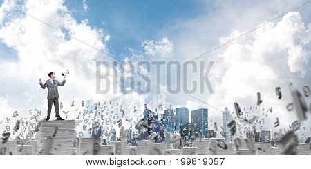 Businessman in suit standing among flying letters with speaker in hand and with skyscape on background. Mixed media.