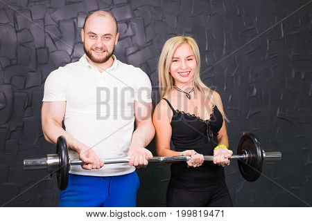Portrait of sporty couple with barbell smiling at camera