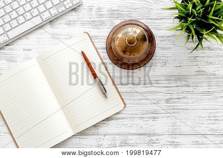 Book hotel. Service bell and notebook at the reception on light wooden table top view.