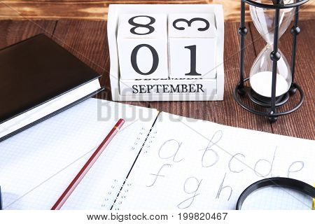 Handwritten Alphabet In Notebook With Office Stationery On Brown Wooden Table