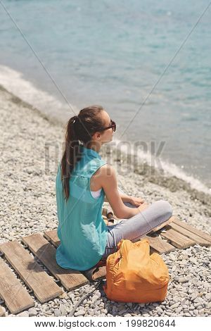Young laughing girl with small orange backpack sits on the wooden coverage on the beach on background of sea