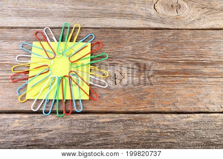 Yellow Reminder Note With Paperclips On Wooden Table