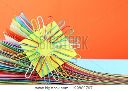 Stack Of Colored Papers With Paperclips On Orange Background