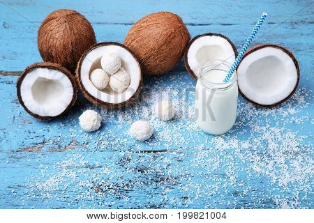 Coconuts And Flakes And Bottle Of Milk On Blue Wooden Table