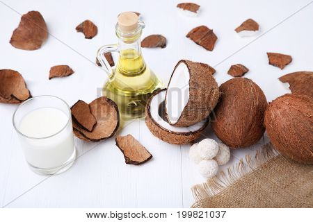Coconuts With Candies And Bottle Of Oil On White Wooden Table