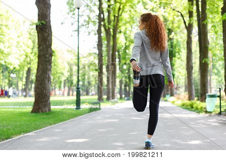 Young female runner warming up before running at morning park, back view