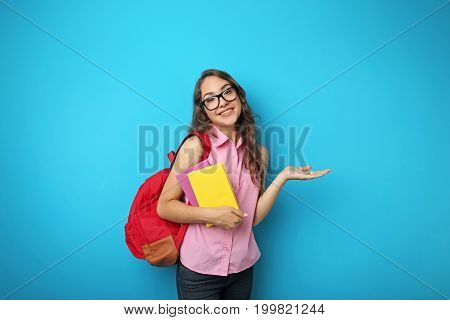 Portrait of student girl with backpack and books on blue background