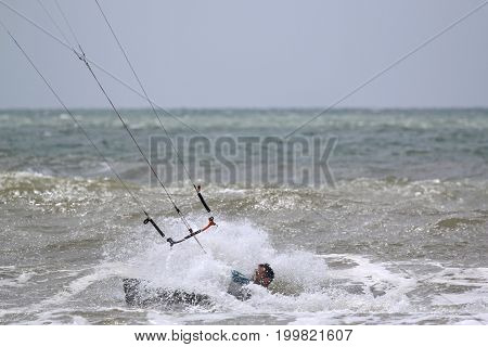 kitesurfer riding his board on the waves