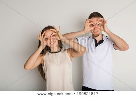 Having fun. Young couple grimacing to camera on white background, copy space