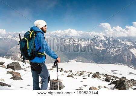 Portrait of a bearded guide with a backpack and an ice ax and sticks for Nordic walking in a hat and sunglasses against the background of snow-capped mountains.