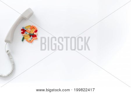 Call doctor. Phone and with pills on white background top view.