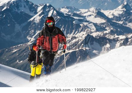 The climber climbs the snow-covered summit. The concept of overcoming difficulties and achieving the goal