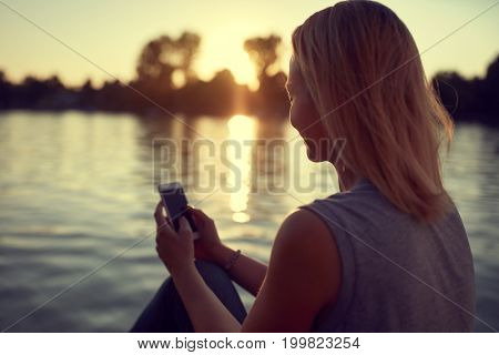 Woman near water with cellphone on sunset, back view