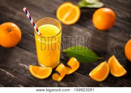 Freshly squeezed orange juice with half oranges on wooden table