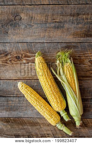 Ripe corn on cobs on rustic wooden table top view.