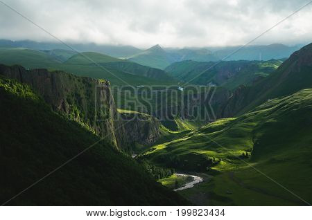The green valley at the foot of the northern side of the elbrus with a mountain river at the bottom of the gorge and beautiful rays of light falling through the clouds.