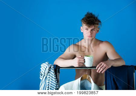 Macho with muscular torso. Clothes hanging on rack. Fitness and fashion concept. Model in wardrobe or dressing room. Man holding cup copy space