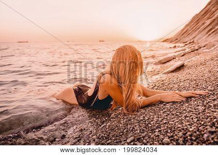 Beautiful woman in black swimwear relax on sea with warm sunset colors.