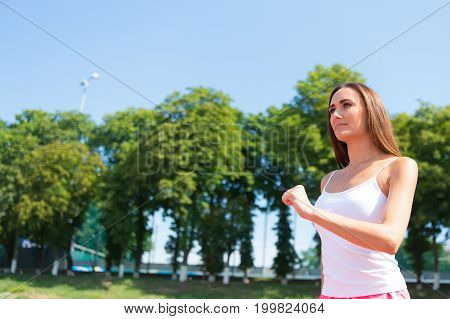 Woman running on arena track. Coach or trainer at workout. Runner on competition and future success. Girl sunny outdoor on blue sky. Sport and healthy fitness.