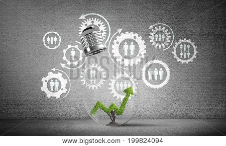 Lightbulb with green growing graph inside placed against sketched social gear structure on grey wall. 3D rendering.