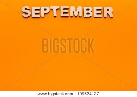 Word Septenber made of wooden letters on orange background. Month planning, timetable concept