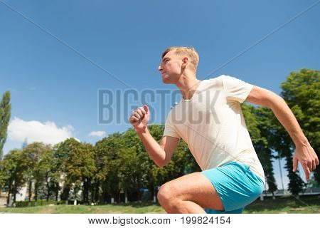 Man running on arena track. Coach or trainer at workout. Runner on competition and future success. Guy sunny outdoor on blue sky. Sport and healthy fitness.