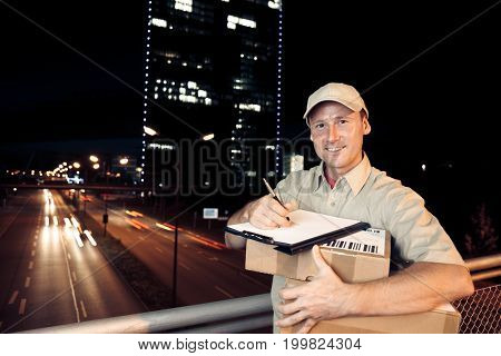 delivery person working at night, buildings and motion-blurred traffic in the backgroound. long exposure. all data on parcel - barcodes, numbers, addresses, etc - are purely fictional and designed by myself