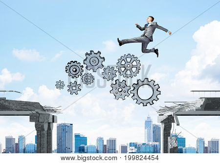Businessman jumping over gap with gear mechanism in concrete bridge as symbol of overcoming challenges. Cityscape on background. 3D rendering.
