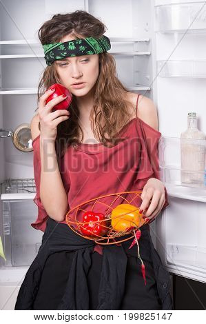 Woman holding sweet peppers at fridge with open door on white background. Healthy food and dieting concept.