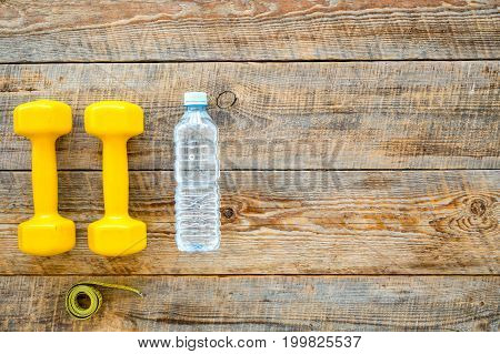 Fitness for loosing weight. Dumbbells, measure tape and water on wooden background top view.