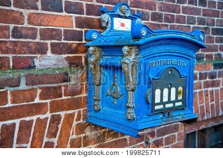 Post Box Blue Color On Red Brick Wall Background