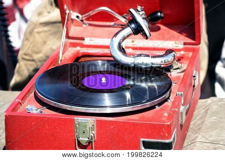 Old red gramophone and old gramophone record on it