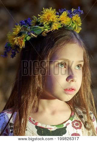 Young Pretty Girl In Flowers Wreath Is Staying Near The Woodpile  In The Village. The Beautiful Witc