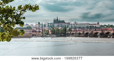 View of the Old Town, Prague Castle, St. Vitus Cathedral, the Charles Bridge and the river Vltava. Vertical shot. Cityscape with dramatic sky. Travel Czech Republic. Europe.