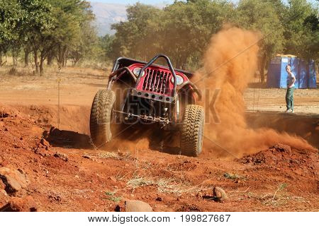 Red Car Climbing Out Steep Dugout Kicking Up Sand And Dust.
