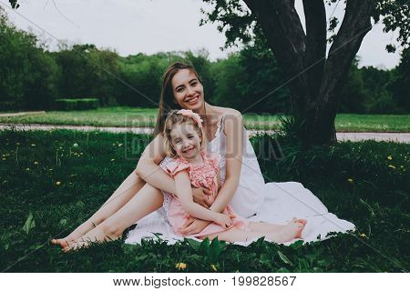 Smiling mother and daughter hugging sitting on the grass.