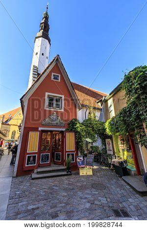 TALLINN ESTONIA - JULY 26 2017: Red building facade and tall tower of church of Holy Spirit in the old town of Tallinn Estonia on July 26 2017