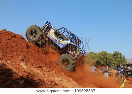 Blue Car Powering Up Steep Sand Mountain, Front Wheels Suspended