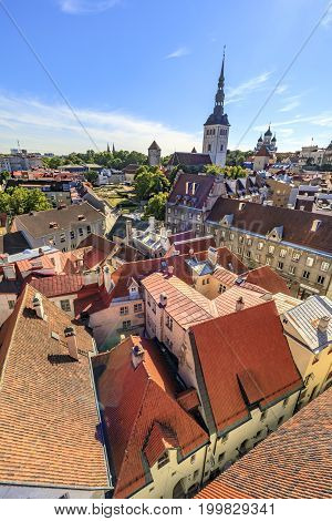 TALLINN ESTONIA - JULY 26 2017: Church St. Nicholas and red roofs of the buildings in the old town of Tallinn Estonia on July 26 2017