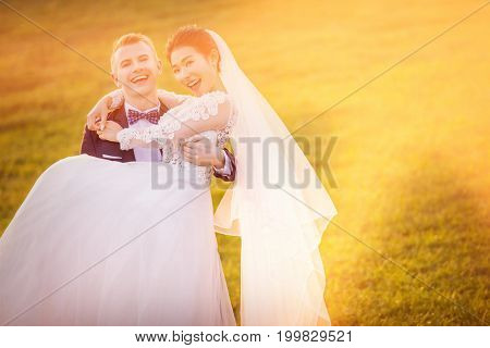 Portrait of cheerful bridegroom carrying bride on grassy field