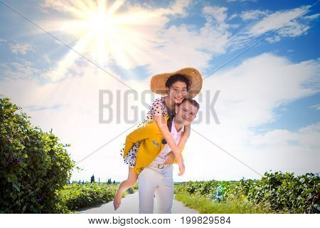 Portrait of happy man piggybacking woman on footpath amidst field against cloudy sky