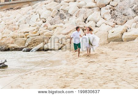 Happy just married young wedding couple celebrating and have fun at beautiful beach.