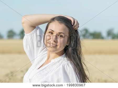 Beautiful sexy smiling female touching her long hair in wheat field