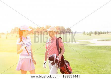Male and female golfers communicating at golf course