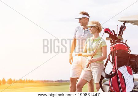 Smiling man and woman standing at golf course against clear sky