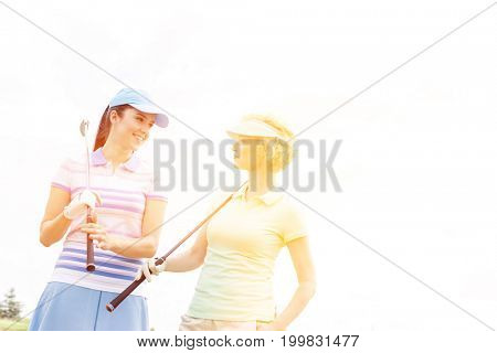 Happy female golfers looking at each other against clear sky