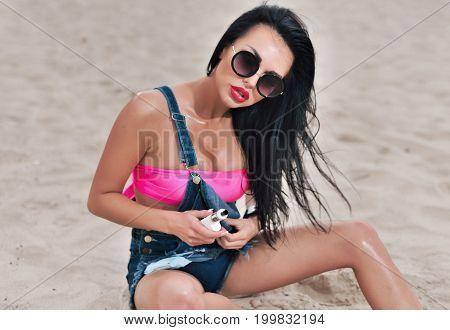 Happy Fashion Smiling Woman In Sunglasses Smoking Vape On Beach