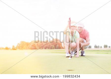 Man assisting woman aiming ball on golf course against clear sky